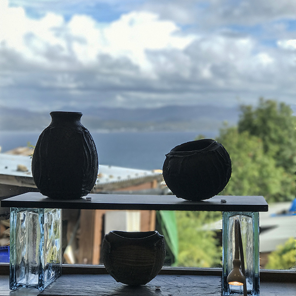 Patricia shone, pots on shelf against Skye view