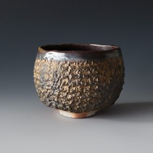A bowl for drinking, wood fired with gilt slip glaze and tenmoku interior glaze
